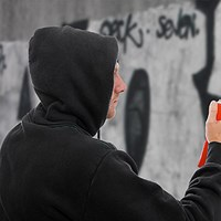 hooded man doing grafitti