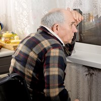 Elderly man looking out the window