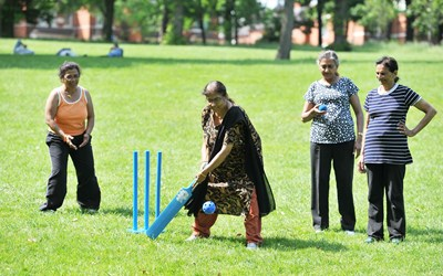 Women playing cricket in a park