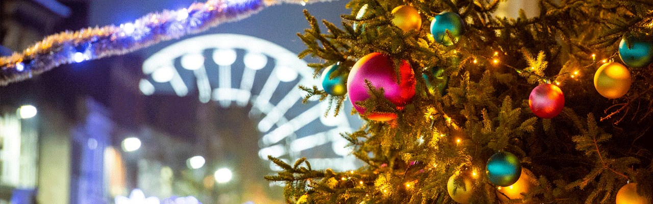 close up of christmas tree and baubles, wheel of light in the background